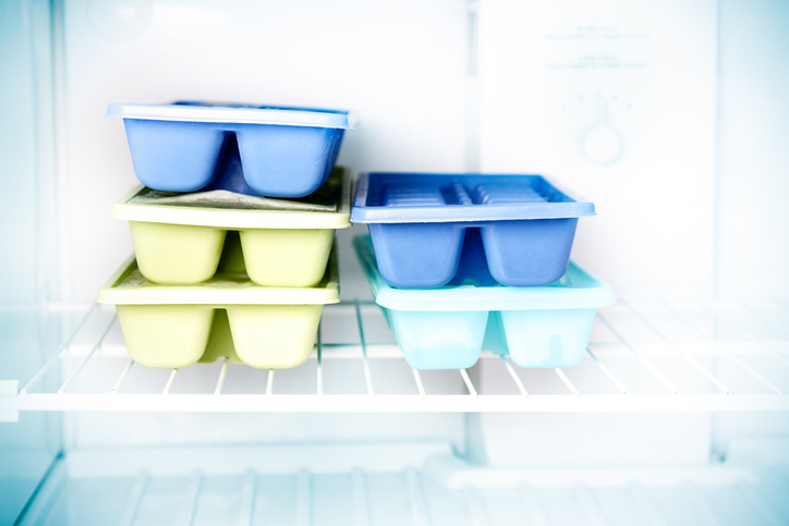 Stacked ice cube trays in a freezer