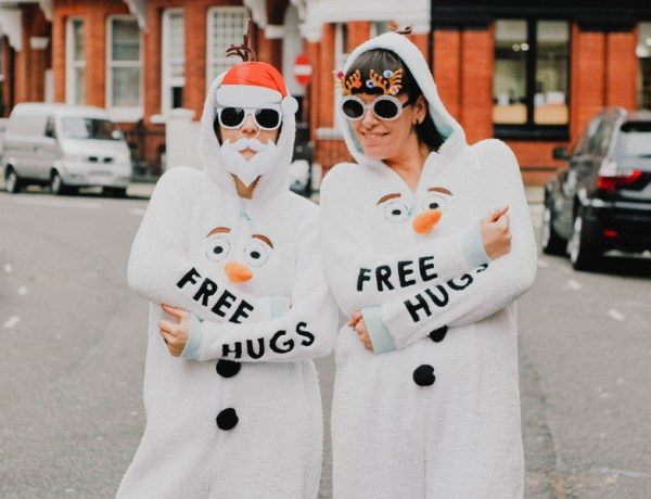 "2 women in snowmen onsies that say ""Free Hugs"""