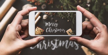 Hands holding iPhone with Merry Christmas message on screen