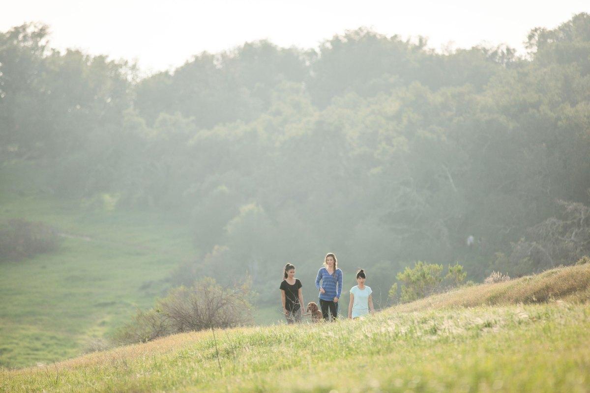 girl wearing a little black dress with friends walking through a field