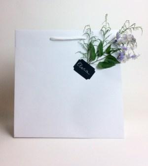 sac cadeau en papier blanc orné de fleurs naturelles