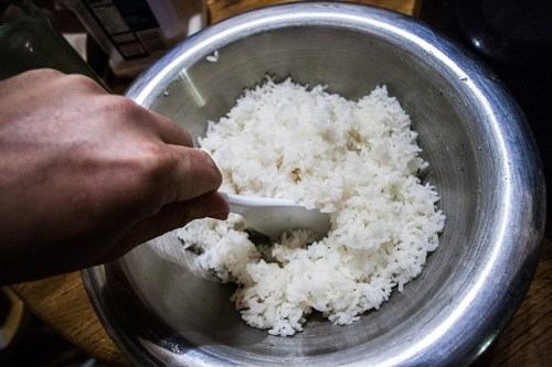 Mixing the rice once the vinegar has been added.