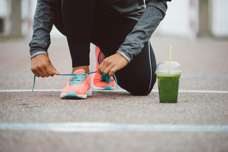 Fitness workout and healthy nutrition concept. Smoothie drink and running footwear close up. Female athlete tying sport shoes laces before training outdoor.