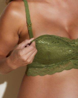 Woman wearing green lace maternity style bralette.