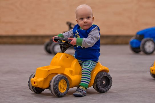 little boy wearing blade and rose tractor outfit on a ride on tractor - Cotswold Baby Co