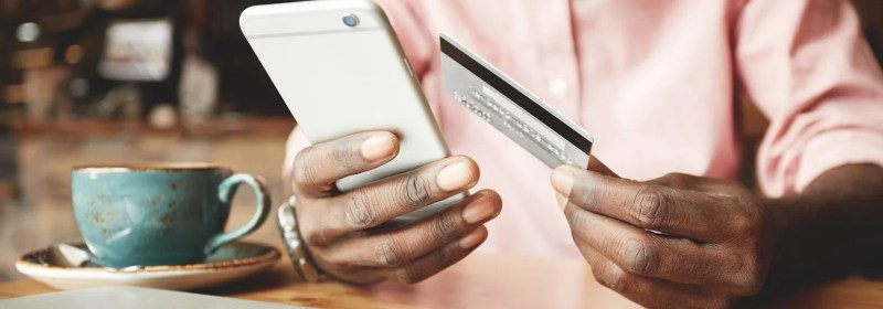 A developer holding a smartphone and a credit card checks the saga pattern on visible on the device.