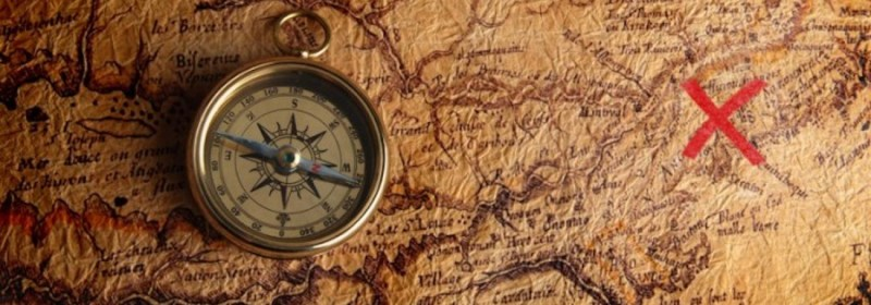 A compass laid atop a map with a red X marking a proposed destination