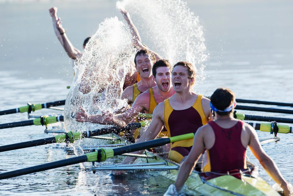 Rowing team splashing and celebrating in scull on lake