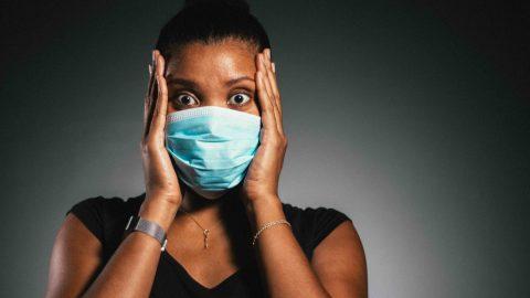 femme portant un masque chirurgical tient sa tête