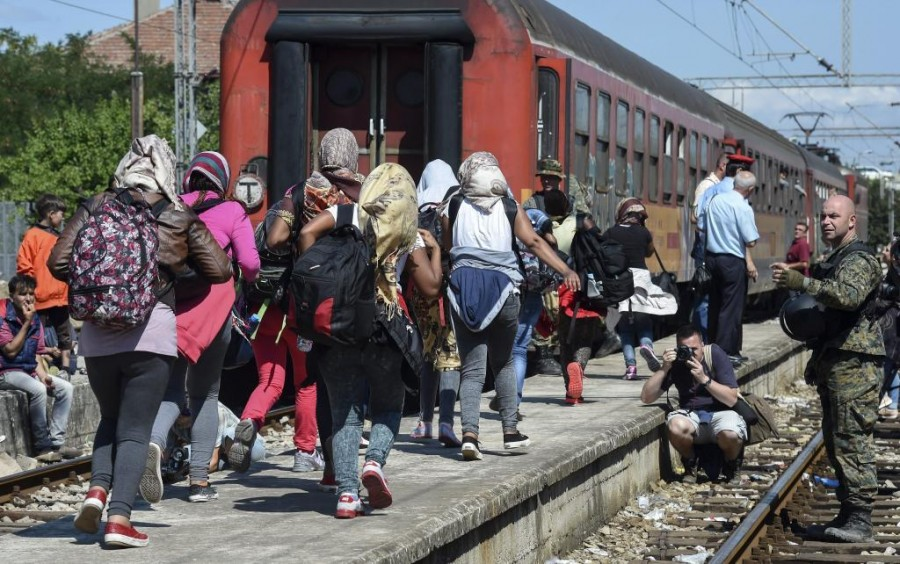 Macedonian police officers control departure of the migrants in the train heeding to the Serbian border