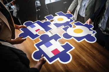 A group of coworkers hold puzzle pieces are making an HQ Trivia logo