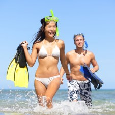 Couple finished snorkeling and emerging from the waves in Maui Hawaii
