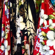 Brightly colored fabrics depict hibiscus blooms. Souvenier shirts are for sale at every shop on the Hawaiian islands.