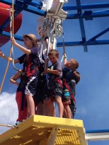 Family harnessed in and tackling the elevated ropes course