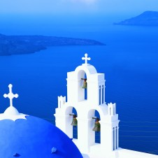 Greek churches with bells ovelooking ocean