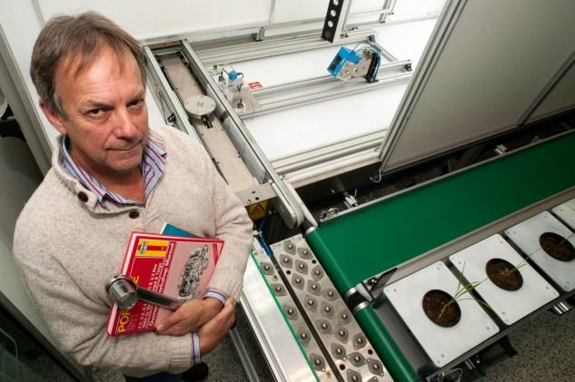 Bob Furbank standing next to the Plant Scan machine with a mechanic's handbook