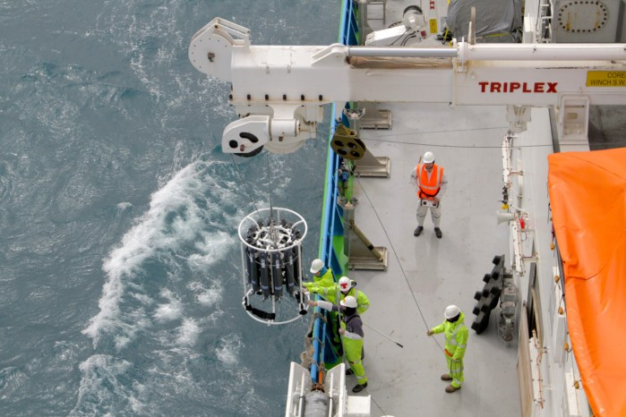 Sampling equipment being lowered into ocean from crane on ship