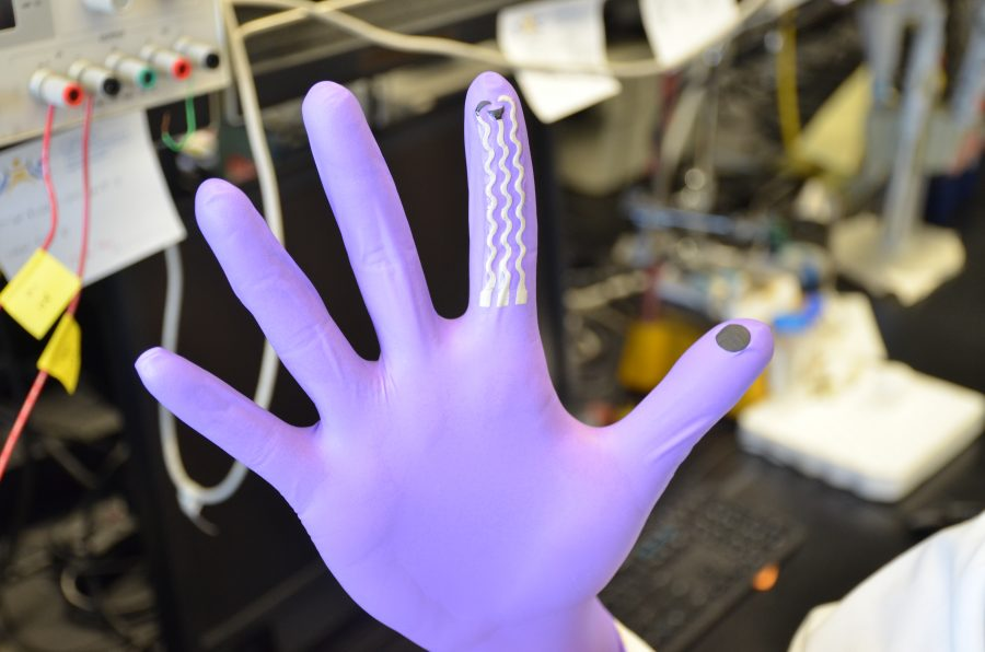 """hand in purple glove, fingers out stretched, three grey """"wave"""" lines running down the index finger, black circle on thumb pad. background: blurred computers and cables in a lab setting."""