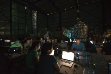 Scientists in the main hangar working on the payloads