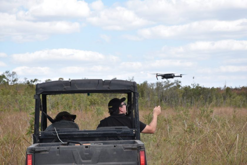 Two men in cart with drone beside it