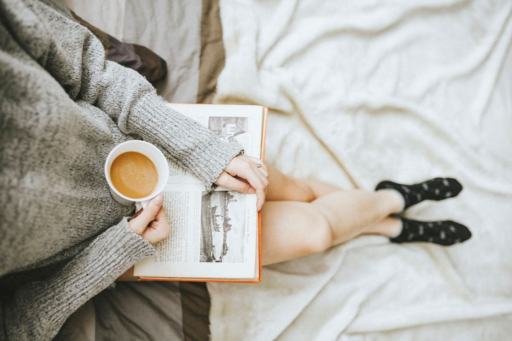 woman holding a cup of coffee at right hand and reading book on her lap