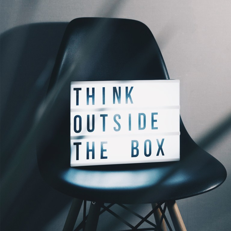 think outside the box sign is placed on dark chair