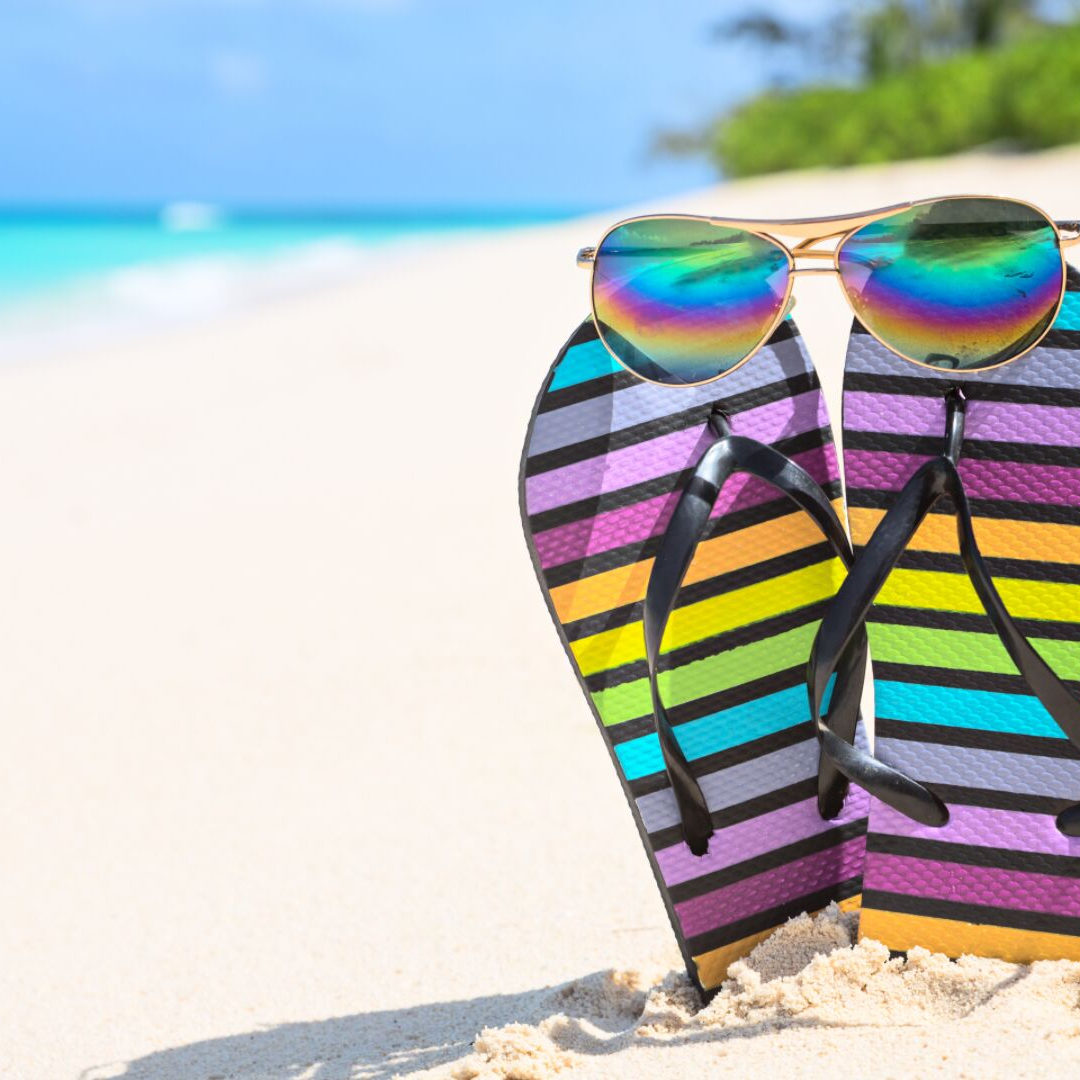 Colorful flip flops and sunglasses on the beach
