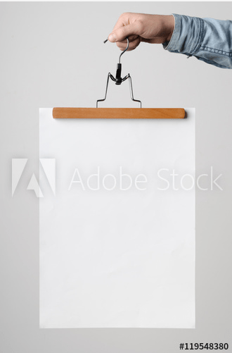 a blank poster is being held by a hand and a hanger