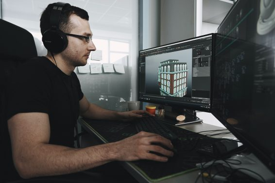 a man working on a 3D model of a house on a gaming pc