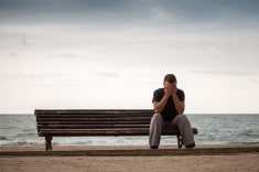 sad-man-sits-on-old-wooden-bench-on-sea-coast