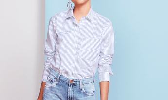 Calça feminina mom jeans clara e camisa branca com listras em azul e detalhe de bolso no lado esquerdo.