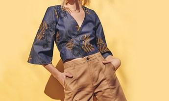 Bermuda feminina de alfaiataria na cor bege escuro no comprimento médio com blusa em tecido jeans com estampa de folhagens, decote alongado e mangas 3/4.