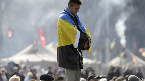 Украин байрағымен жамылған ер адам.