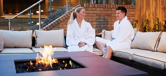 Image of man and woman relaxing in the outdoor spa garden at David Lloyd Clubs.