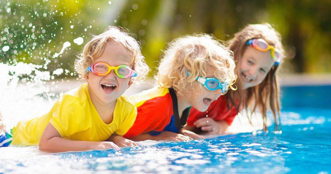 3 children playing in a swimming pool