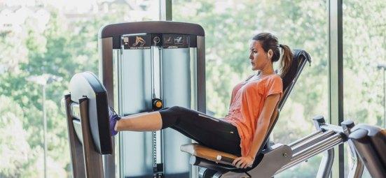 Lady on leg press in gym