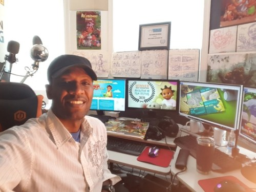 Solomon W. Jagwe at his desk with Nkoza and Nankya art in the background