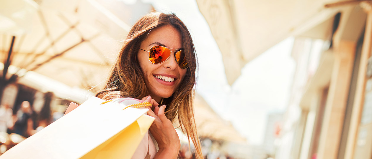 lady smiling outside store holding shipping bags