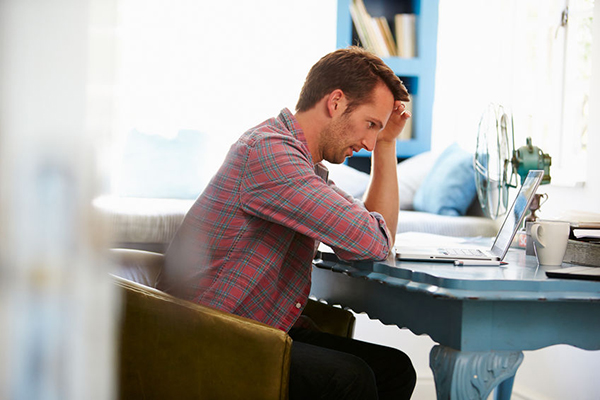 41393393 - stressed man at desk in home office with laptop