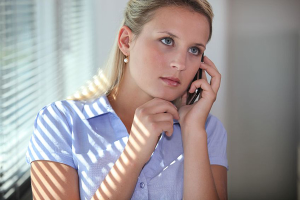 17977269 - young woman using a cellphone in an office