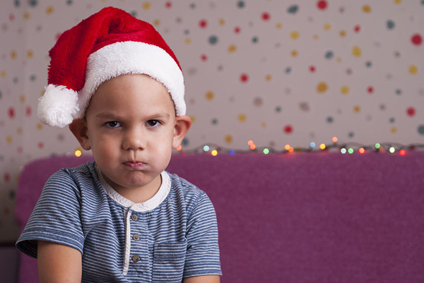 88690732 - boy in a santa hat angrily looks