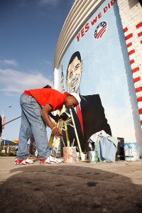 Sergio Toussaint painting a mural picturing president elect Barak Obama.