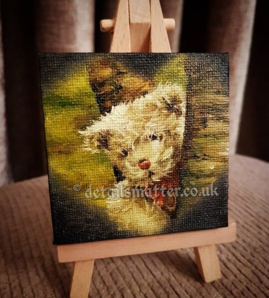 Canvas painting of cream teddy with red bow peeking out between trees displayed on a miniature easel