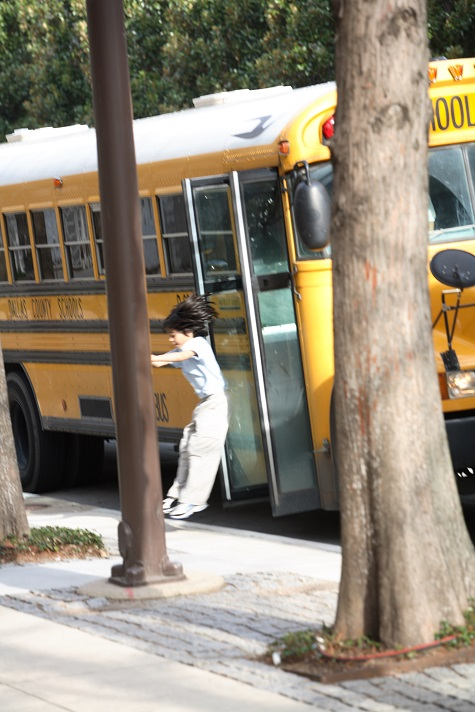 Student jumping off of a school bus at the DMA.