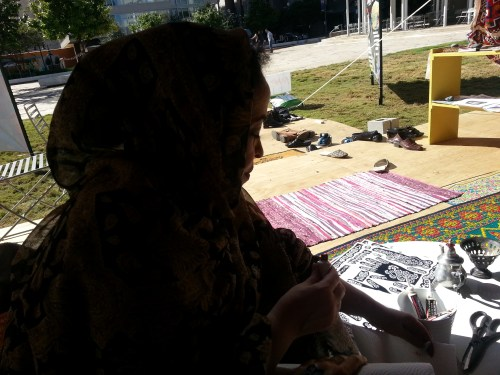 Najat prepares the stencil and henna ink for tattoos.