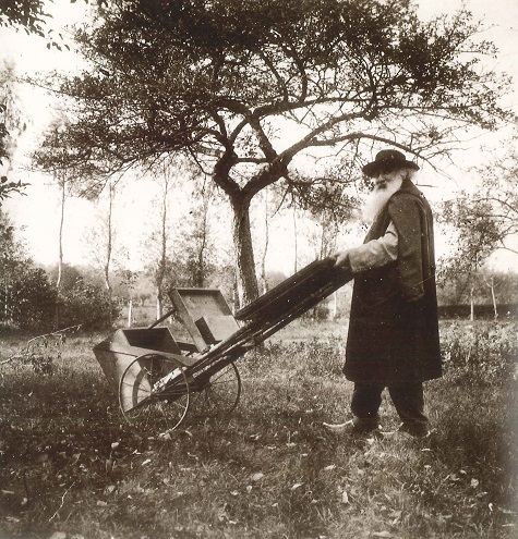 Camille Pissarro taking his rolling easel outdoors to paint near his house in Éragny, France, c. 1895