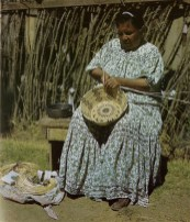 Basket weaver Lizette Phillips is in the process of weaving a coiled basket. Notice the raw materials nearby. Photograph by Robert H. Peebles, 1954.