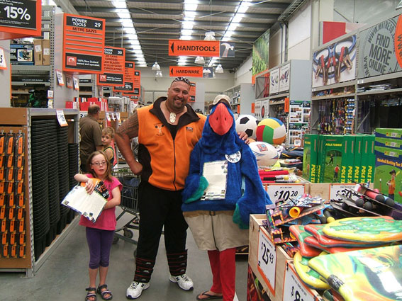 Sacha in takahe suit posing with Mitre 10 'Big is Good' giant Levi Vaoga and a small girl.