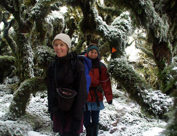 Sacha with friend amongst twisted, snow covered trees, wrapped up warm, packs on backs.