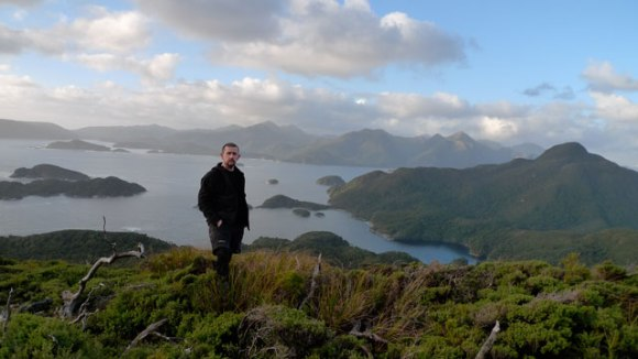 Chris Birmingham standing on on a peak at dusk with various islands behind him.